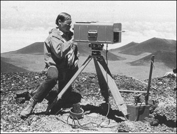 Black and white image of a person using a geodimeter